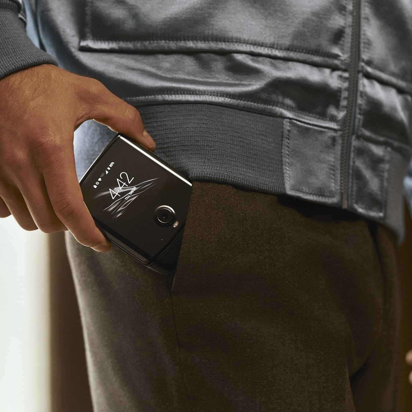 A man putting his motorola razr in his pocket