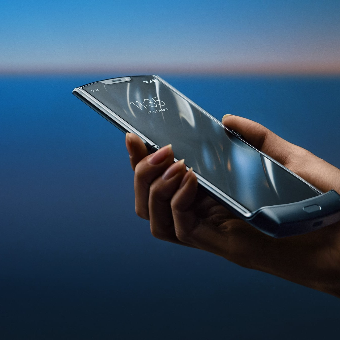 A hand holding an open Motorola Razr